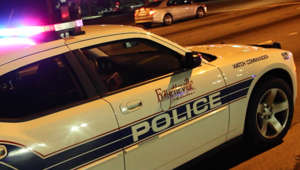 a car parked in front of a bus: Fayetteville Police investigate homicide
