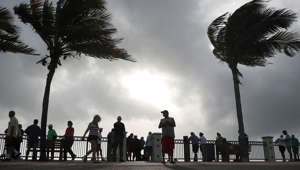People stand at the water's edge of the Atlantic Ocean as winds from Hurricane Dorian pick up on September 2, 2019 in Vero Beach, Florida.