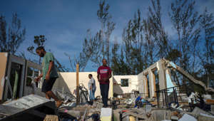 George Bolter, left, and his parents walk through the remains of his home destroyed by Hurricane Dorian in the Pine Bay neighborhood of Freeport, Bahamas, Wednesday, Sept. 4, 2019. Rescuers trying to reach drenched and stunned victims in the Bahamas fanned out across a blasted landscape of smashed and flooded homes Wednesday, while disaster relief organizations rushed to bring in food and medicine. (AP Photo/Ramon Espinosa)
