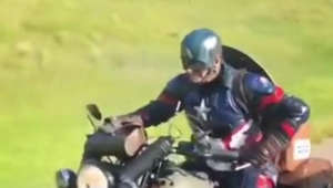 Man dressed as superhero rides bike and gives passerby his visiting card