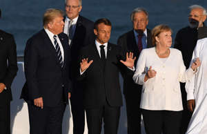BIARRITZ, FRANCE - AUGUST 25: US President Donald Trump, France's President Emmanuel Macron, Germany's Chancellor Angela Merkel join G7 leaders and guests as they gather for a family picture in front of the Biarritz lighthouse on the second day of the annual G7 summit on August 25, 2019 in Biarritz, France.  (Photo by Andrew Parsons - Pool/Getty Images)