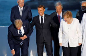 French President Emmanuel Macron, U.S. President Donald Trump, and German Chancellor Angela Merkel react as they pose for a family photo with invited guests during the G7 summit in Biarritz, France, August 25, 2019.  REUTERS/Philippe Wojazer