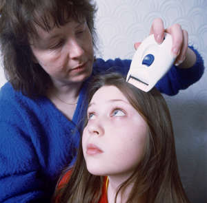 10 year old girl with dry hair bein nit combed for head lice by her mother using an electronic niz zapper, UK. (Photo by: Photofusion/Brian Mitchell/UIG via Getty Images)