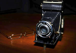 Vintage old photographic camera and glasses. Spot lighting, black background.