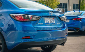 a blue car parked in a parking lot: Versa vs. Yaris: Subcompact Sedan Battle