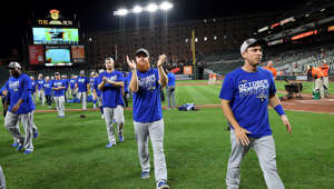 Los Angeles Dodgers' Justin Turner, center, and others celebrate as they walk off the field after a baseball game against the Baltimore Orioles, Tuesday, Sept. 10, 2019, in Baltimore. The Dodgers won 7-3, clinching the NL West title. (AP Photo/Nick Wass)
