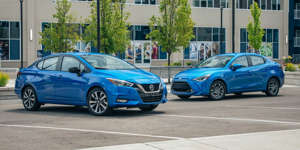 a blue car parked on a city street: Balancing practicality and a smidge of fun between Nissan's new Versa and Toyota's Mazda-sourced Yaris.