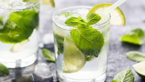 Mojito cocktail with lime and mint in glass at sunlight. Closeup photo.
