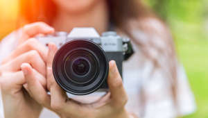 closeup front lens of mirrorless camera in woman teen photographer