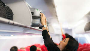 Traveler and tourism woman open overhead locker on airplane ,Hand-luggage compartment with suitcases in airplane. Hands take off hand luggage. Passenger put cabin bag cabin on the top shelf. Travel concept