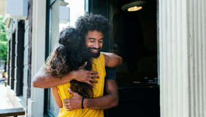 Two friends greeting each other and embracing outside a restaurant.