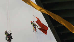 Greenpeace activists try to hang from bridge for 24 hours