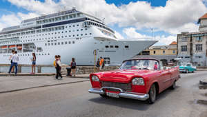 Havana, Cuba - May 27, 2018 : MSC Cruises Armonia Cruise Ship at harbor of Havana Cuba with vintage car driving on road in front