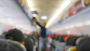 Blurred passenger putting luggage in overhead locker on the airplane