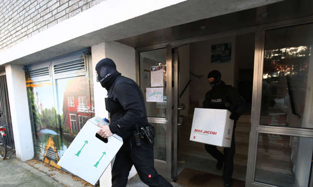 11 September 2019, Hamburg: Policemen carry boxes from a house. On Wednesday morning, police took action against suspected terror supporters during raids in several northern German states. Officials had searched several objects in Hamburg, Schleswig-Holstein and Mecklenburg-Western Pomerania.