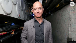 Jeff Bezos standing in front of a car