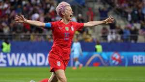 a person holding a football ball: US captain Megan Rapinoe celebrates scoring her team's ninth goal against Thailand in the World Cup.