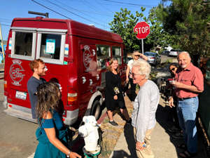 a group of people standing around a bus: Those stops in Alameda and Oakland became magnets for neighbors desperate to see each other.