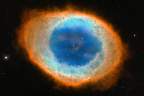 "This image shows the dramatic shape and color of the Ring Nebula, otherwise known as Messier 57. From Earth's perspective, the nebula looks like a simple elliptical shape with a shaggy boundary. However, new observations combining existing ground-based data with new NASA/ESA Hubble Space Telescope data show that the nebula is shaped like a distorted doughnut. This doughnut has a rugby-ball-shaped region of lower-density material slotted into in its central ""gap"", stretching towards and away from us."