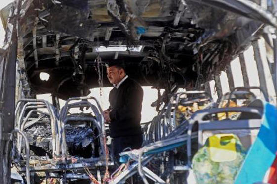 Explosion: An Egyptian policeman inspects the damaged bus after the deadly bombing in Taba.