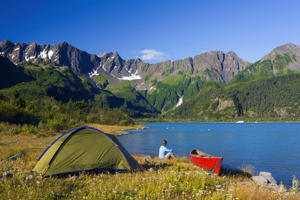 Woman Camping On An Island Via Canoe On Bear Glacier Lake, Kenai Fjords National Park, Kenai Peninsula, Southcentral Alaska, Summer