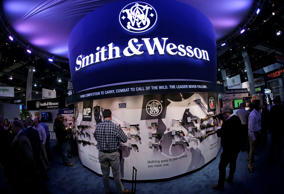 Trade show attendees examine hand guns and rifles in the Smith & Wesson display boot at the Shooting Hunting and Outdoor Tradeshow, Tuesday, Jan. 14, 2014, in Las Vegas.