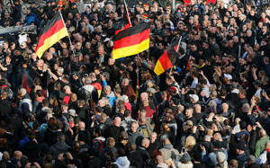 People gather with German national flag during a demonstration by 'hooligans against Salafists and Islamic State extremist' in Cologne October 26, 2014.