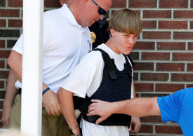 Police lead suspected shooter Dylann Roof, 21, into the courthouse in Shelby, North Carolina, on June 18, 2015.   Roof, a 21-year-old with a criminal record, is accused of killing nine people at a Bible-study meeting in a historic African-American church in Charleston.  U.S. officials are investigating the shooting as a hate crime. Jason Miczek/Reuters