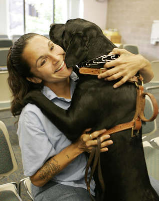 ** ADVANCE FOR WEEKEND EDITIONS, OCT. 8-9 **Prison inmate Anita Goulet hugs Cole, one of two  service dogs she helps train, at the state prison for women in Shakopee, Minn. Goulet, shown during an interview Sept. 29, 2005, is serving time for drunk driving and will be eligible for release in 41 months.  Women are the fastest-growing segment of the U. S. prison population. Corrections officials from around the country will gather next week in Bloomington, Minn., to talk about how to deal with the rising number of women behind bars. (AP Photo/Jim Mone)