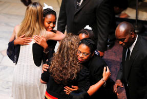 Eliana Pinckney (L) and mother Jennifer (C) hug mourners as the late South Carol...