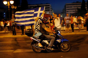 A supporter of the No vote waves a Greek flag after the first results of the referendum at Syntagma square in Athens, Sunday, July 5, 2015. Greece faced an uncharted future as its interior ministry predicted Sunday that more than 60 percent of voters in a hastily called referendum had rejected creditors' demands for more austerity in exchange for rescue loans.