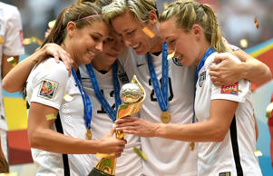 (From left) Alex Morgan, Lauren Holiday, Abby Wambach and Whitney Engen of the United States hold the championship trophy after their 5-2 win over Japan in the FIFA Women's World Cup on July 5, 2015, at BC Place Stadium in Vancouver, British Columbia, Canada.