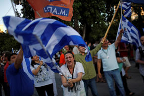 A supporter of the No vote waves a Greek flag after the referendum's exit polls at Syntagma square in Athens, Sunday, July 5, 2015. Emilio Morenatti/AP