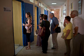 People wait their turn to cast their vote at a polling station in Athens, Sunday, July 5, 2015. Emilio Morenatti/AP