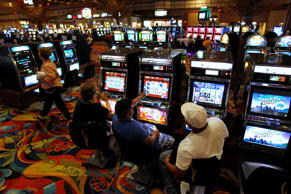 FILE - Patrons play slot machines at the Twin River Casino, in Lincoln, R.I. Steven Senne/AP