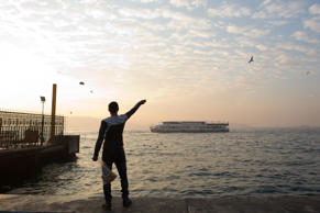 File: A man throws bread to birds from the bank of the Bosphorous as a tourist boat passes in Istanbul, Turkey, on Wednesday, Jan. 15, 2014.