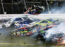Austin Dillon (3) goes airborne and hits the catch fence as he was involved in a multi-car crash on the final lap of the NASCAR Sprint Cup series auto race at Daytona International Speedway, Monday, July 6, 2015, in Daytona Beach, Fla.