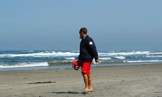 A Life Guard looks back on the ocean after clearing the water following a fatal shark attack off Solana Beach, California April 25, 2008.