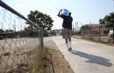 Paul Reid carries a case of bottled water on April 23 in Porterville, Calif. Over 300 homes in the California central valley city of Porterville are living without running water after their wells dried up due to the severe drought.