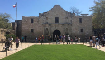 Visitors walk at the entrance to the Alamo, the most-visited tourist site in the state, in San Antonio, Texas on March 2, 2015.