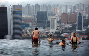 Tourists relax in an infinity pool on the roof of the Marina Bay Sands Hotel tower  in Singapore.