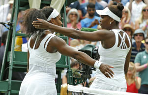 Serena Williams of the United States, left hugs her sister Venus Williams of the United States after winning their singles match, at the All England Lawn Tennis Championships in Wimbledon, London, Monday July 6, 2015. Serena Williams won 6-4, 6-3.