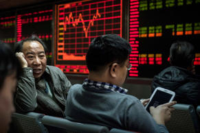Chinese day traders chat as they sit in front of stock tickers on a board at a brokerage firm Beijing, China.