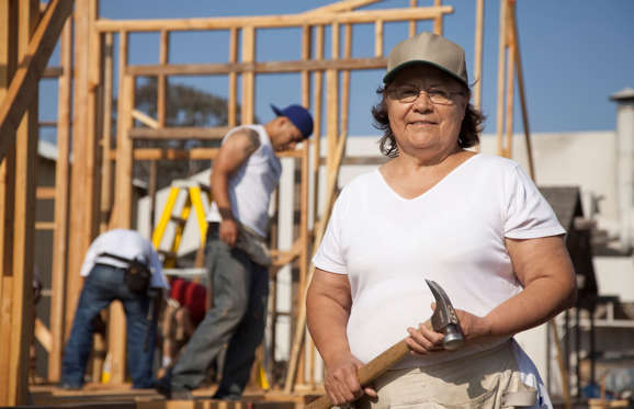 Woman holding hammer at construction site.