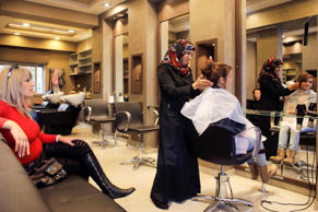 "A Palestinian hairdresser works with Israeli Jewish customers at a hairdressing salon, owned by a local Palestinian woman, at the Palestinian neighbourhood of Beit Safafa in Jerusalem December 2, 2014. The city has long been divided. Western districts are mostly Jewish while Palestinians live to the east - over the invisible ""Green Line"" that marked the line separating Israel and Jordan until a 1967 war when Israeli forces took over East Jerusalem."