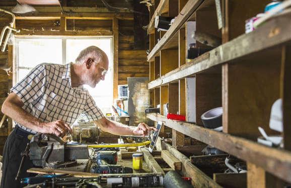 Confident senior carpenter sitting in workshop.