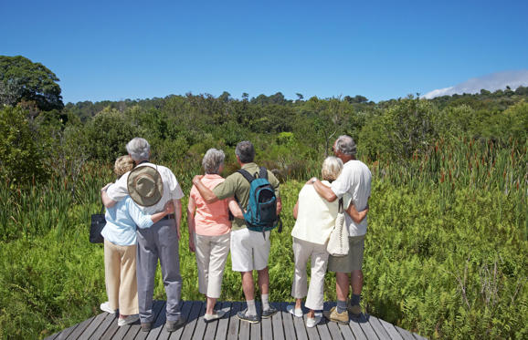 Three senior couples looking at view in gardens.