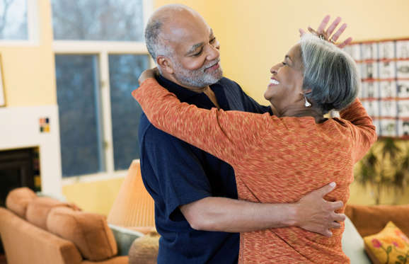 Couple dancing in their home.