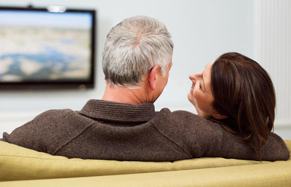 Mature couple sitting on sofa watching television.