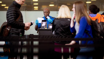A Transportation Security Administration (TSA) officer checks a passenger's identification and boarding pass at a security checkpoint at Ronald Reagan National Airport (DCA) in Washington DC.